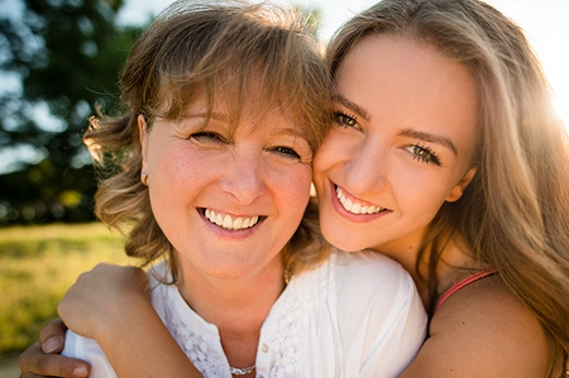Mother and daughter with healthy teeth and bright smiles.
